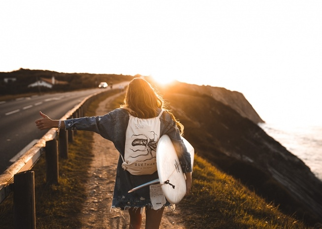 - Nature poster showing a surfer looking to hitch a ride with her surfboard under her arm at sunset.