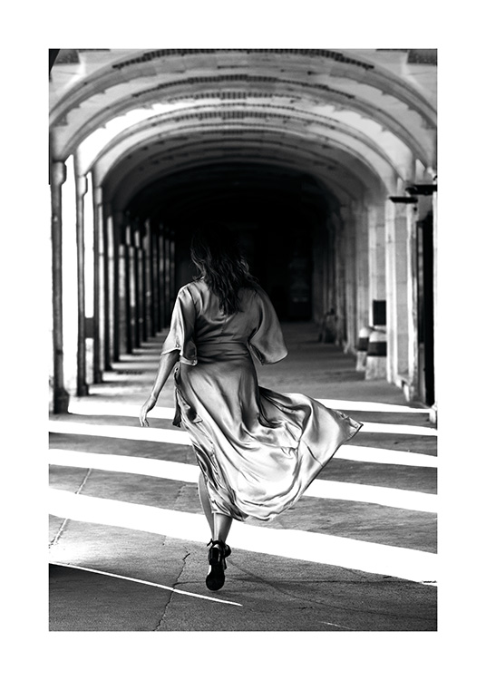 - Black and white poster of a woman in a dress running through a colonnade.