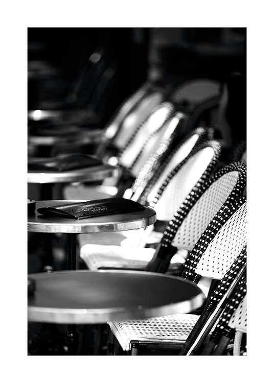 - Poster in black and white with the sun shining on the outdoor area of a Paris café.
