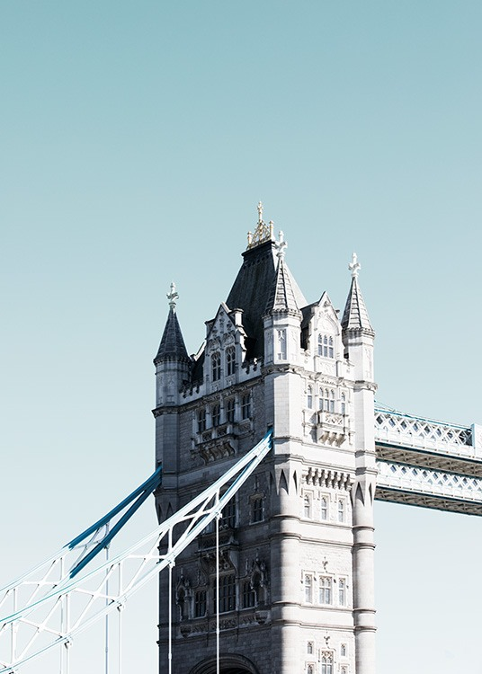 - Close-up shot of a tower of Tower Bridge in London against a light-blue background.