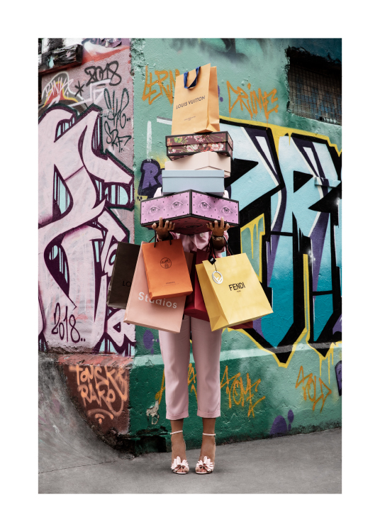 – Photograph of a woman holding shoe boxes and shopping bags in front of a graffiti wall