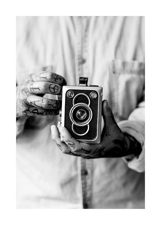 – Black and white photograph of a vintage camera being held by a man with tattoed hands