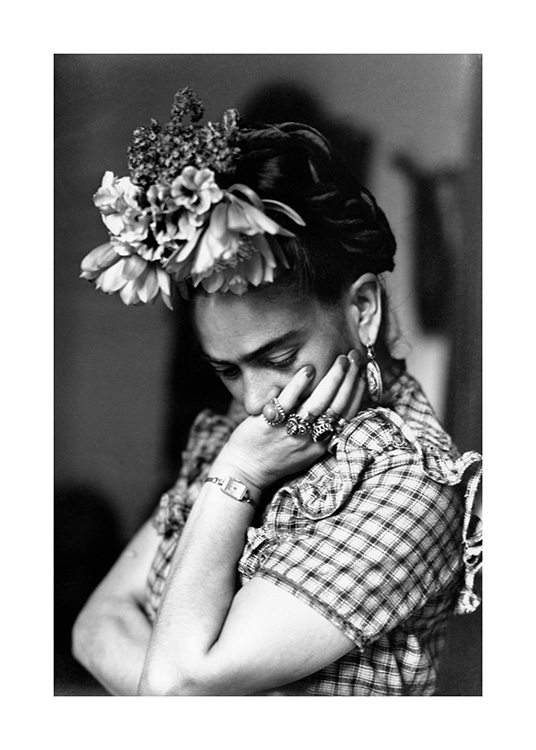 – Black and white photograph of Frida Kahlo with flowers in her hair and her chin in her hand