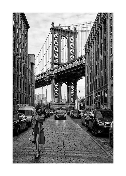 – Black and white photograph of a woman standing in a street in New York in front of Manhattan Bridge