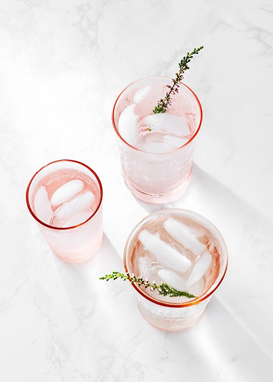 Photo of three pink drinking glasses with sprigs, standing on marble
