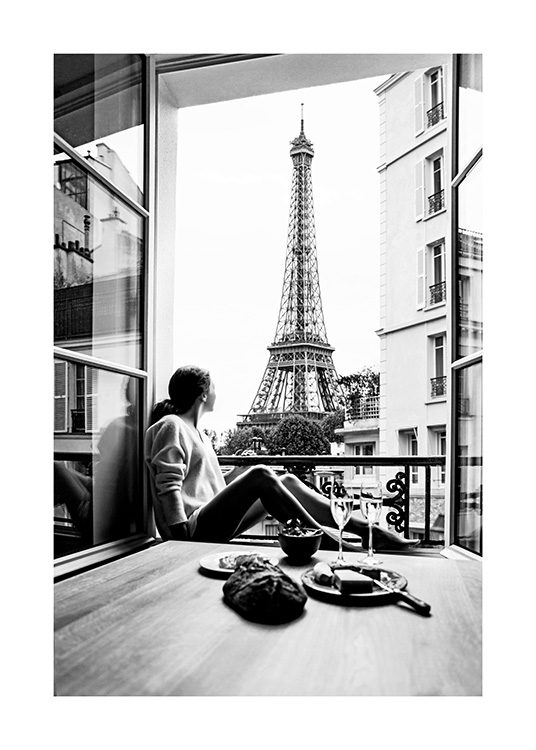 Black and white photo from Paris featuring a woman in a window and the Eiffel Tower in the background