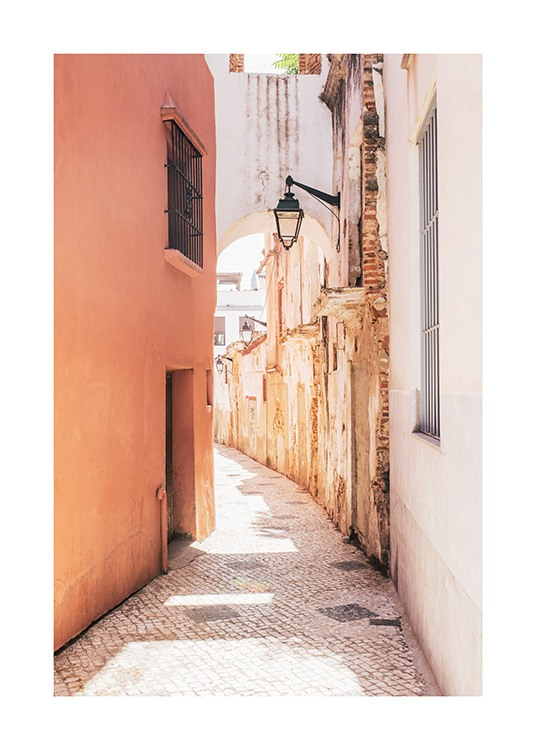 Street in Spain with walls in orange and white, with a street lamp in the middle