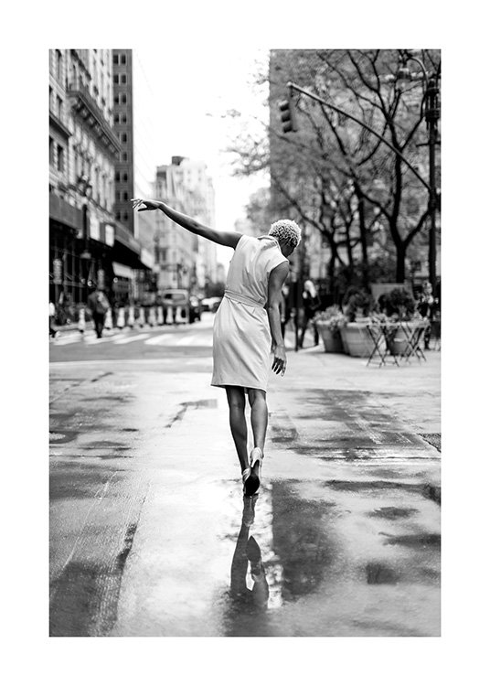 Woman wearing dress standing on wet street in New York with hand stretched up
