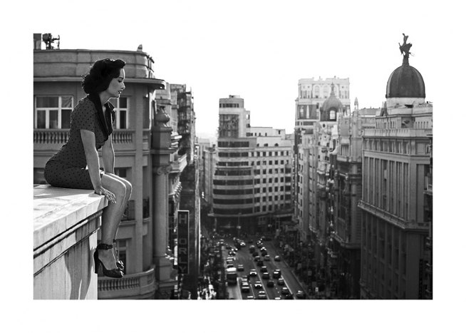 Black and white photograph of woman looking down at city from rooftop