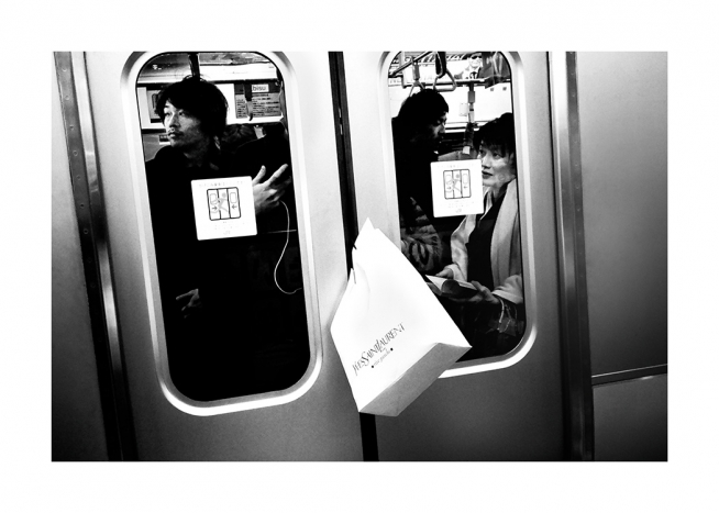 Black and white photograph of shopping bag caught between train doors