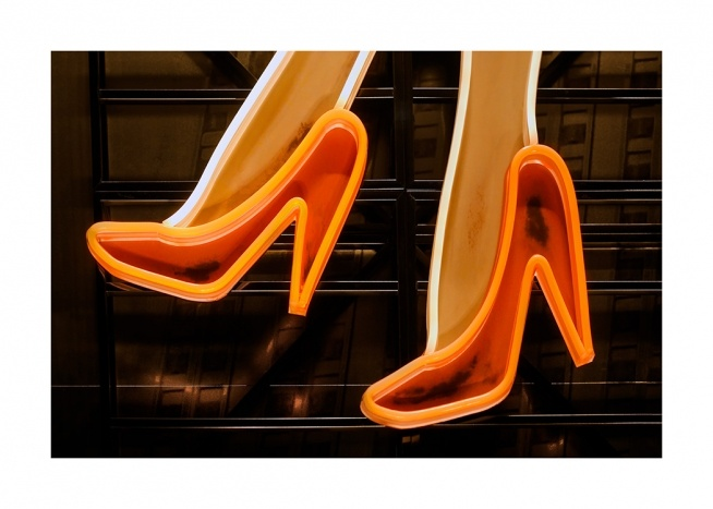 - Photograph of orange neon sign of heels on a dark background