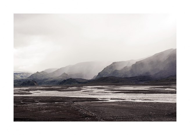 - Photograph of landscape with water puddles and mountains covered in fog