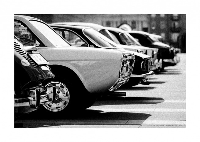 - Black and white photograph of a line of retro vintage cars in a parking lot