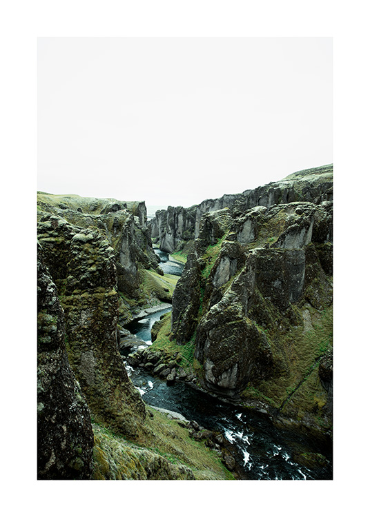 - Photograph of green mountain landscape with river flowing between cliffs