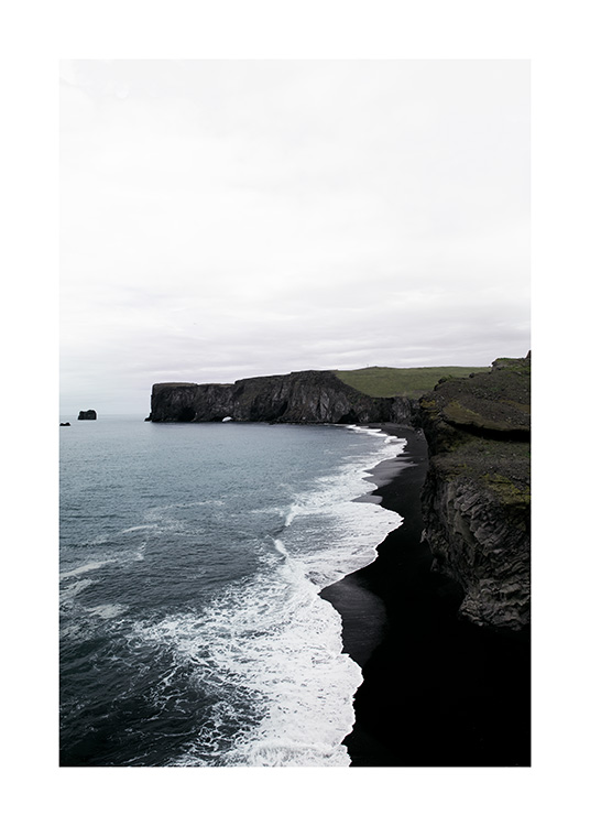 - Photograph of coast with black cliffs, black beach and ocean waves