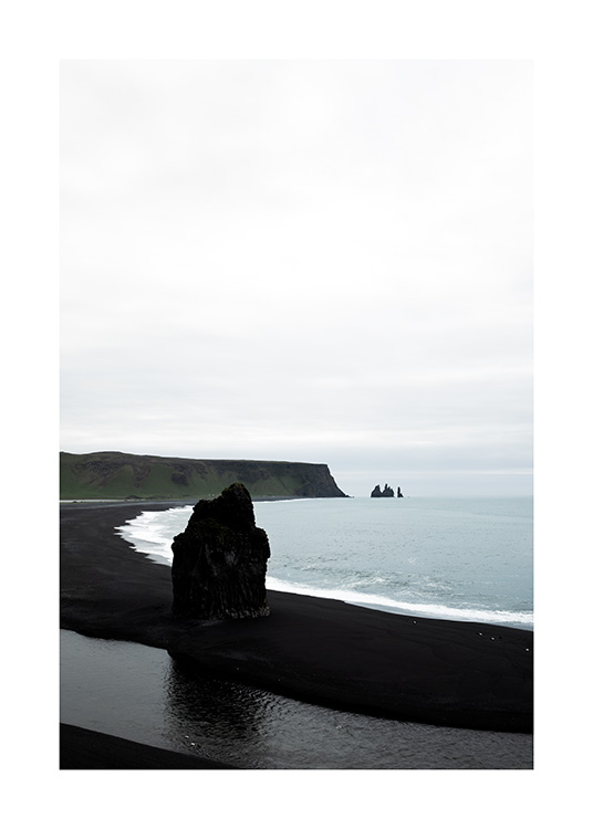- Photograph of ocean and bay with black sand beach and black cliffs