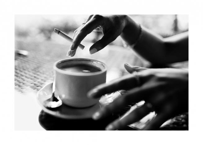 - Black and white photograph of a coffee cup and hands holding a cigarette