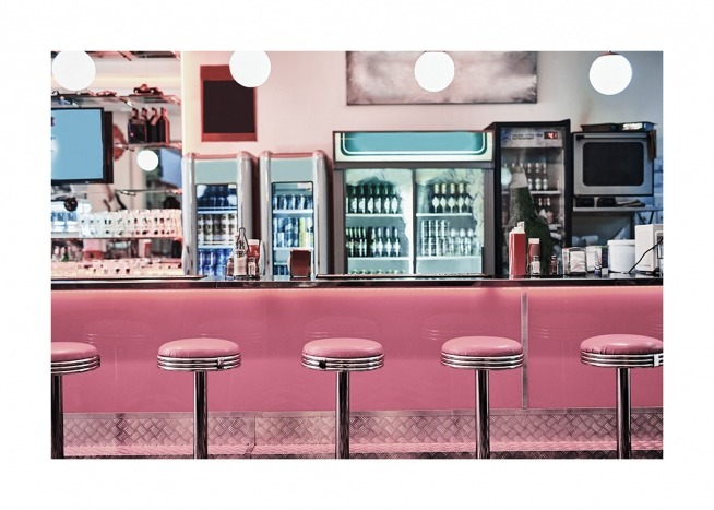 - Photograph from a vintage diner with pink bar chairs in front of a pink bar