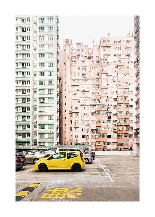 - Photograph from Hong Kong with a yellow car in front of pastel apartment buildings in green and peach