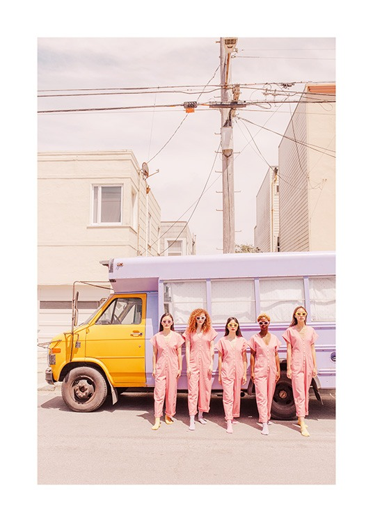 - Photograph of girls wearing pink jumpsuits standing in front of a truck in light purple and yellow