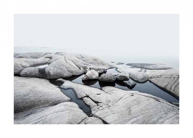 – Photograph of a coastline with smooth rocks and water inbetween them
