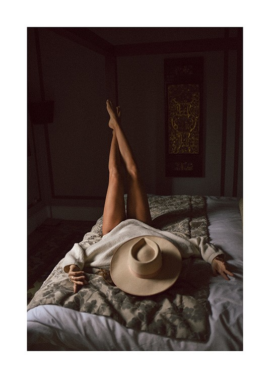 – Photograph of a woman laying on a bed with her legs stretched up into the air and a hat covering her face