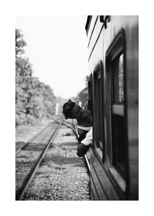 – Black and white photograph of a couple kissing each other in an open window of a train