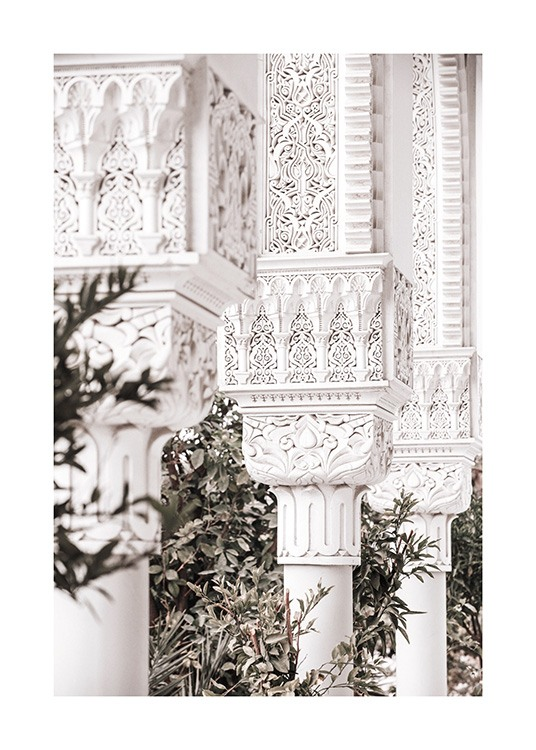 - Photograph of crafted white pillars with patterns and green leaves in the background