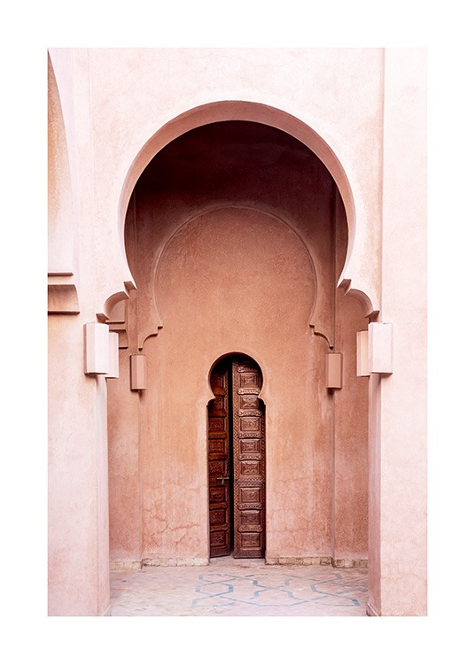 - Photograph of a pink building with curved arches and a narrow, brown door in the middle