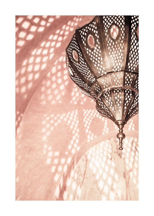 - Photograph of a pink room with a metal lamp reflecting a pattern on the walls