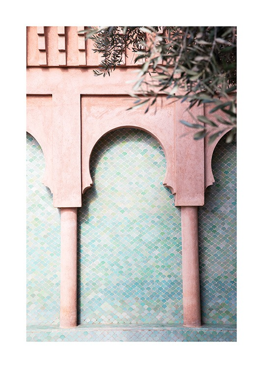 - Photograph of pink pillars and curved arches on a blue, mosaic wall with leaves in the foreground