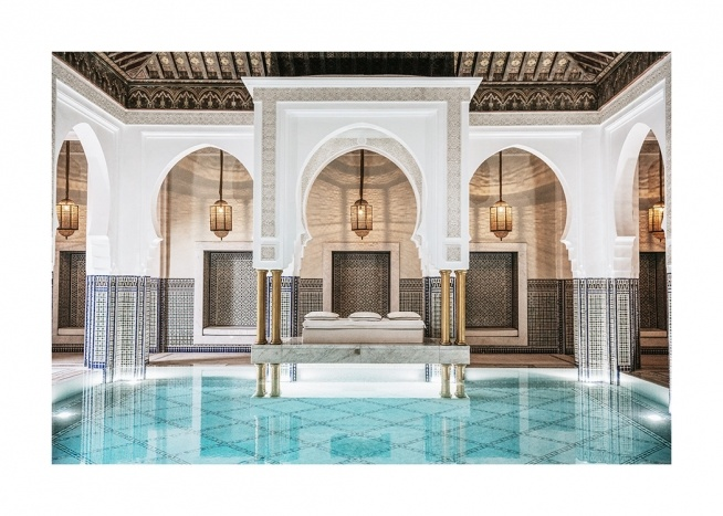 - Photograph of a room with golden lamps, white, curved arches and a pool