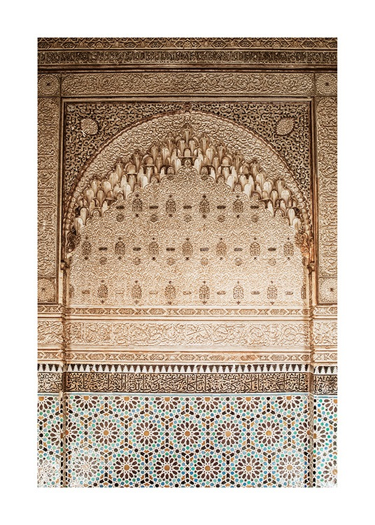 - Photograph of a golden wall with carvings and a pattern in mosaic at the bottom