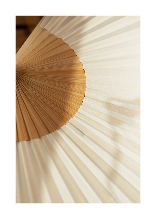 – Photograph of a white folding fan with a wood coloured centre