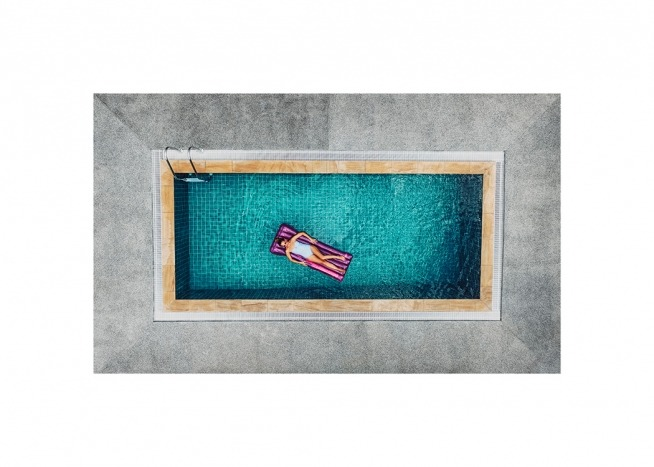 – Aerial photograph of a woman resting on a mattress floating in a blue pool