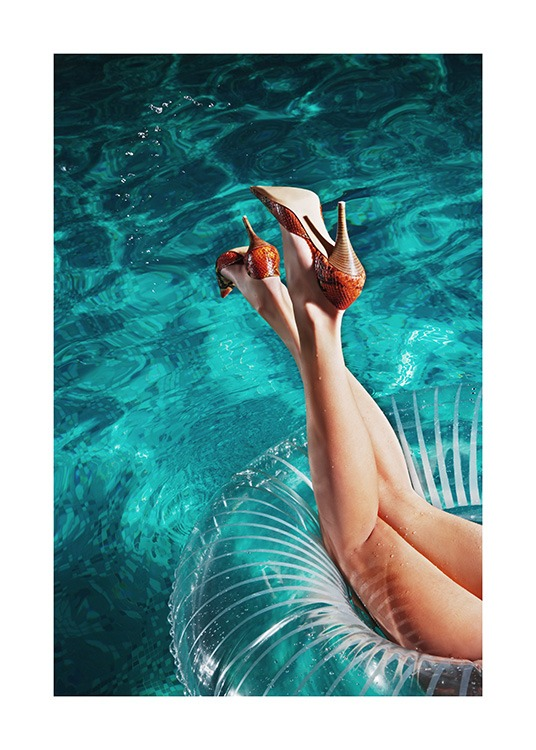 – Photograph of a pair of legs and high heels in a swim ring in a pool
