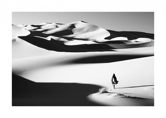 – Black and white photograph of a desert, with a woman walking in the sand dunes