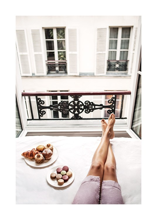 – Photograph of plates with buns and macarons next to a pair of legs in a window
