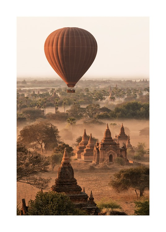 – Photograph of a red air balloon above a landscape with trees and temples covered in fog