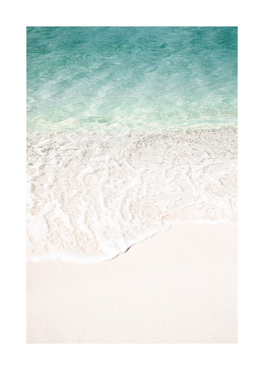 – Photograph of clear blue water and a beach with white sand