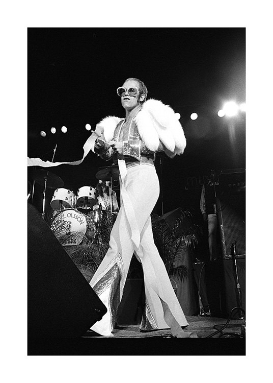 – Black and white photograph of the singer Elton John, wearing a white jumpsuit and sunglasses on stage