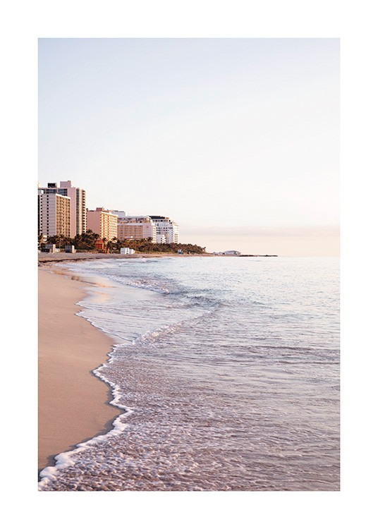 – Photograph of waves washing up on a beach in Miami with buildings in the background