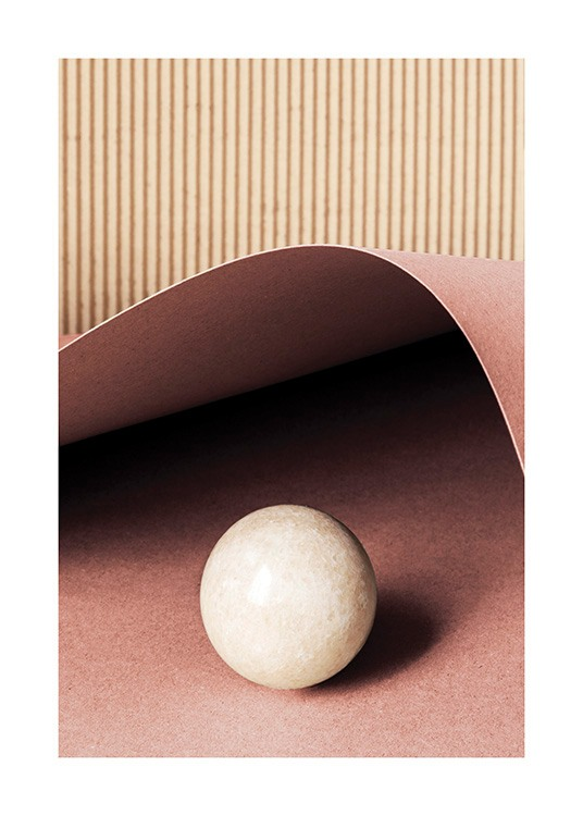 – Photograph of a beige ball in stone laying on a red piece of paper, with a striped background