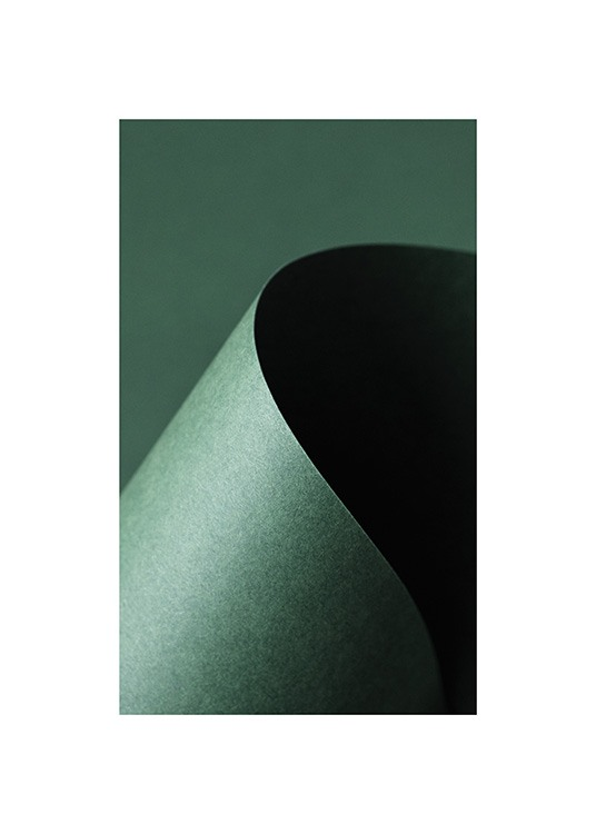 – Photograph of a green paper shaped into a curve, against a dark green background