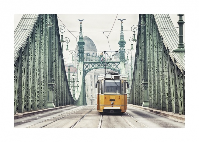 – Photograph of a vintage, yellow tram on a green bridge in Budapest with buildings in the background