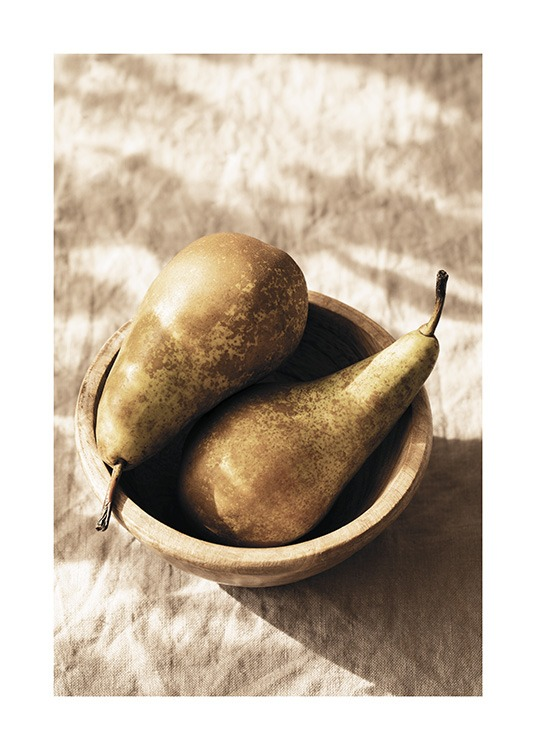– Photograph of a pair of pears laying in a wooden bowl on a beige linen cloth
