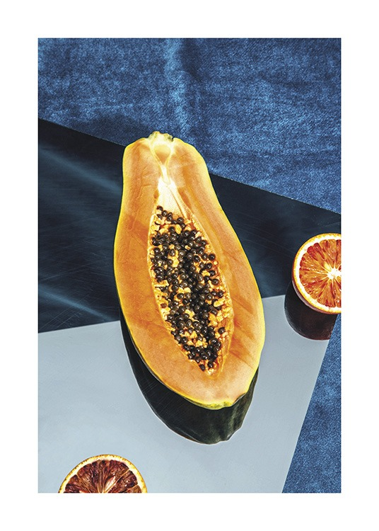 – Photograph of a papaya laying on a blue, colour blocked background with oranges next to it