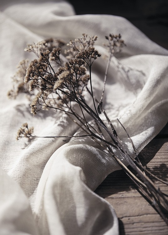 – Photograph of dried flowers in a bundle, with a white linen cloth underneath them