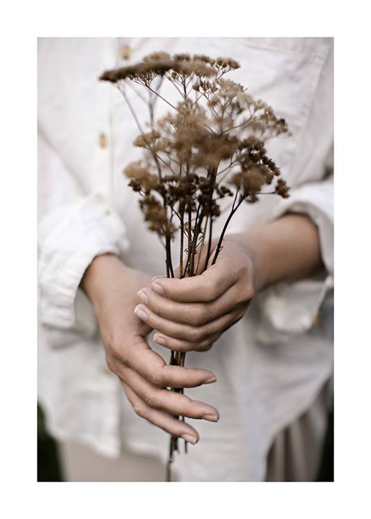 – Photograph of a woman holding a bouquet with dried flowers, with her white linen shirt in the background