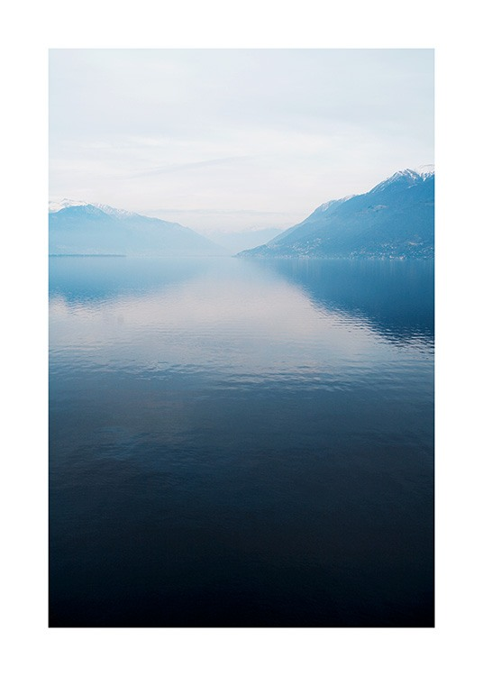 – Photograph of a lake with a still surface, with mountains and fog in the background